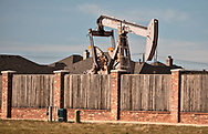 Active pump jack in next to homes in Midland Texas.