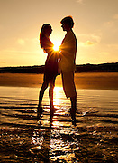 Ad campaign: Couple silhouetted at sunset on Praia Grande beach on Ilha do Mel, Brazil
