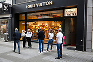to comply with the distance rules during the Corona pandemic, customers are waiting in front of the Louis Vuitton store on the shopping street Hohe Strasse, Cologne, Germany.<br /> <br /> zur Einhaltung der Abstandsregeln waehrend der Corona-Pandemie warten Kunden vor demLouis Vuitton store in der Hohen Strasse, Koeln, Deutschland.