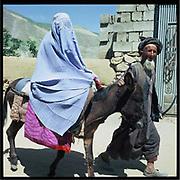 A man takes a woman on a donkey, Badakshan.