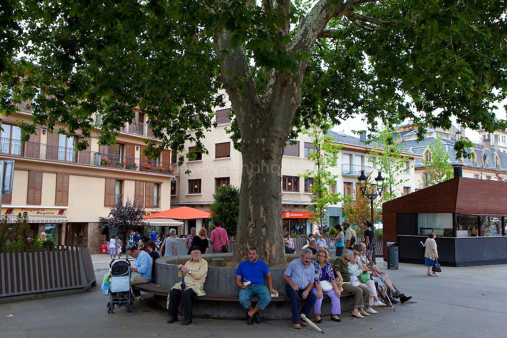 People sitting under a tree in Placa de Santa Maria, Puigcerda, Sunday morning, August 2011