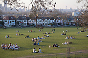 As government Coronavirus pandemic restrictions ease, with the mixing of households within groups of six coming into effect, groups of friends gather on the grass in Ruskin Park, south London, to enjoy warm Spring weather, on 30th March 2021, in London, England.