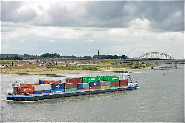 Nederland, Nijmegen, 20-6-2015Een binnenvaartschip geladen met containers vaart over de rivier de waal richting Rotterdam. Op de achtergrond de Waalbrug.Foto: Flip Franssen/Hollandse Hoogte