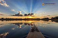 Kayaking into sunset rays on McWennger Slough near Kalispell, Montana, USA