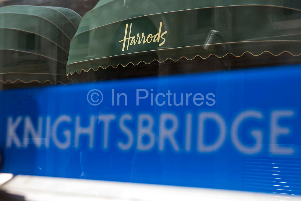 Knightsbridge London Underground sign outside the tube station entrance with the world famous Harrods shop awning in the background, London, United Kingdom.