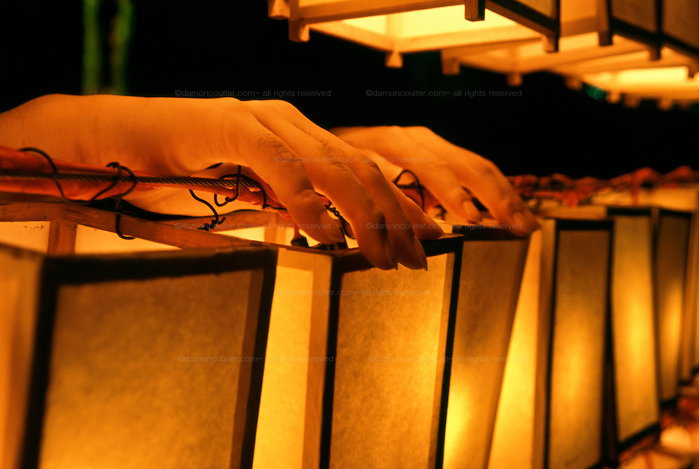 Hands rest on a paper lantern carrying the name of a family member who died in one of Japan's wars at the Mitama matsuri or festival of remembrance for Japanese war dead Yasukuni shrine, Tokyo, Japan, Monday, July 16th 2007