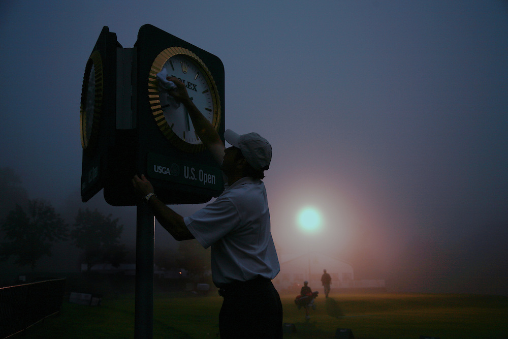 Francois Burgy cleans the face of the official clock as the first player arrives at the driving range prior to the start of the first round of play at the 2007 U.S. Open Championship at Oakmont Country Club in Oakmont, Pennsylvania.