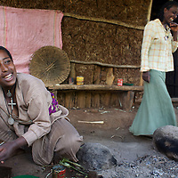 "Wubalem shares a joke while preparing dinner for her family in the kitchen area at the back of her home...Wubalem Shiferaw, age 23, lives in the village of Mecha with her husband Tsega Bekele, age 33, and their daughter Rekebki, age 4. Wubalem remembers her grandparents harvesting honey. She has maintained this tradition while moving to modern hives which produce a far greater yield of honey. Wubalem is a member of the Mecha village Cooperative which brings together local women beekeepers allowing them to share insights and build a credit union. The Mecha village Cooperative is not yet a member of the Zembaba Union. Wubalem's husband Tsega is a priest and a tailor. ..Harvesting honey supplements the income of small farmers in the Ethiopian region of Amhara where there is a long tradition of honey production. However, without the resources to properly invest in production and the continued use of of traditional, low-yielding hives, farmers have not been able to reap proper reward for their labour. ..The formation of the Zembaba Bee Products Development and Marketing Cooperative Union is an attempt to realize the potential of honey production in Amhara and ensure that the benefits reach small producers. ..By providing modern, high-yield hives, protective equipment and training to beekeepers, the Cooperative Union helps increase production and secure a steady supply of honey for which there is growing demand both in and beyond Ethiopia. The collective processing, marketing and distribution of Zembaba's ""Amar"" honey means that profits stay within the cooperative network of 3,500 beekeepers rather than being passed onto brokers and agents. The Union has signed an agreement with the multinational Ambrosia group to supply honey to the export market. ..Zembaba Bee Products Development and Marketing Cooperative Union also provides credit to individual members and trains carpenters in the production of modern hives. ..Photo: Tom Pietrasik.Mecha, Amhara. Ethiopia.November 17th"
