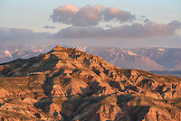 The first light of morning illuminates the McCullough Peak Badlands with the Beartooth Mountains in the distance. It was a very cold and windy morning.