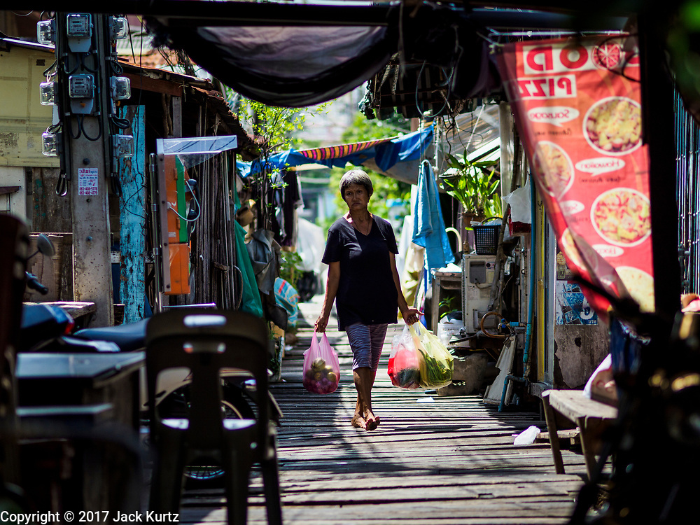 """21 JUNE 2017 - BANGKOK, THAILAND: A woman walks home with her groceries in a community along the Chao Phraya River south of Krung Thon Bridge. This is one of the first parts of the riverbank that is scheduled to be redeveloped. The communities along the river don't know what's going to happen when the redevelopment starts. The Chao Phraya promenade is development project of parks, walkways and recreational areas on the Chao Phraya River between Pin Klao and Phra Nang Klao Bridges. The 14 kilometer long promenade will cost approximately 14 billion Baht (407 million US Dollars). The project involves the forced eviction of more than 200 communities of people who live along the river, a dozen riverfront  temples, several schools, and privately-owned piers on both sides of the Chao Phraya River. Construction is scheduled on the project is scheduled to start in early 2016. There has been very little public input on the planned redevelopment. The Thai government is also cracking down on homes built over the river, such homes are said to be in violation of the """"Navigation in Thai Waters Act."""" Owners face fines and the possibility that their homes will be torn down.          PHOTO BY JACK KURTZ"""