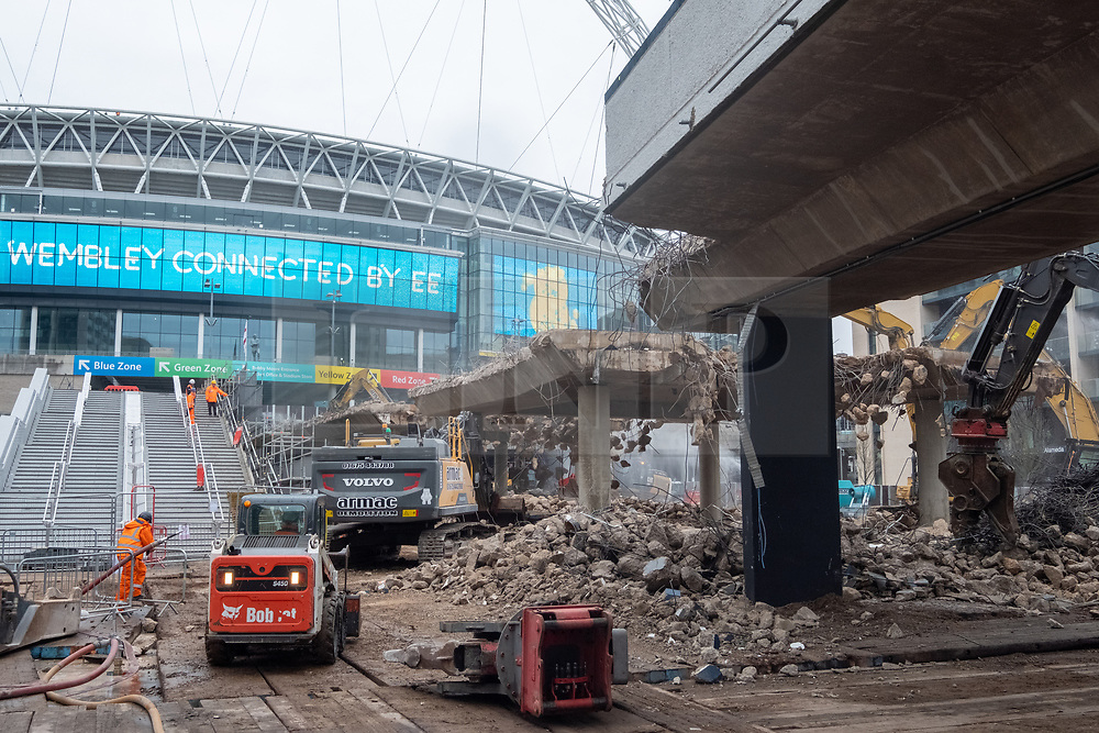 © Licensed to London News Pictures. 20/11/2020. London, UK. The statue of footballer Bobby Moores overlooks the demolition of Wembley Stadium's famous ramp walkway by construction workers. On the left of the photo is the new Olympic staircase. The 46 year old iconic walkway is giving way to the 'Olympic Steps' part of a wider plan to modernize Olympic Way. Photo credit: London News Pictures