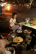 Food for sale at a busy evening street market along the Irrawaddy river in Mandalay, Myanmar