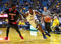 Dec 22, 2018; Morgantown, WV, USA; West Virginia Mountaineers forward Wesley Harris (21) drives baseline against Jacksonville State Gamecocks center Ty Hudson (4) during the second half at WVU Coliseum. Mandatory Credit: Ben Queen-USA TODAY Sports