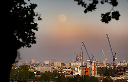 © Licensed to London News Pictures. 06/05/2020. London, UK. The near full Supermoon rises through the haze over central London. Also know as the Flower Moon at this time of year - it will be at it's fullest as it rises later tomorrow. A supermoon is a full or new moon that comes closest to the Earth in its elliptical orbit—resulting in a slightly larger than usual apparent size when viewed from Earth. Photo credit: Peter Macdiarmid/LNP