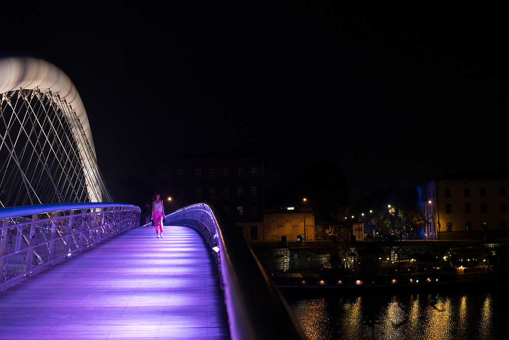 A woman walks at night on the Father Bernatek Footbridge in Krakow, Poland. Accomodating pedestrians and cyclists, this bridge was in 2010 and spans the Wisła River, linking the districts of Kazimierz and Podgórze. Numerous lovers' padlocks are attached the bridge.