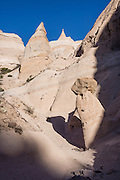 """Hoodoos. See fantastic hoodoos and a great slot canyon in Kasha-Katuwe Tent Rocks National Monument, in New Mexico, USA. Hike the easy Cave Loop Trail plus Slot Canyon Trail side trip (3 miles round trip), 40 miles southwest of Santa Fe, on the Pajarito Plateau. Distinctive cone-shaped caprocks protect soft pumice and tuff beneath. Geologically, the Tent Rocks are made of Peralta Tuff, formed from volcanic ash, pumice, and pyroclastic debris deposited over 1000 feet thick from the Jemez Volcanic Field, 7 million years ago. Kasha-Katuwe means """"white cliffs"""" in the Pueblo language Keresan."""