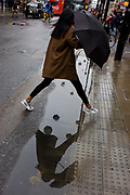 A woman jumps over a puddle after rainfall in Oxford Street, central London. The day is dark and grey in autumnal weather and it feels like a dystopian landscapoe of dirty pavements (sidewalks) and road surfaces. Reflected in the puddle we see spherical lighting features ready for a forthcoming Christmas, echoed on the raised kerbside buttons that help pedestrians cross safely. We see the woman holding her umbrella while half-way across the width, before landing still dry the other side.