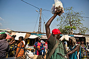 A street vendor, foreground, sells packages of whiskey in a busy market area in Bangui.