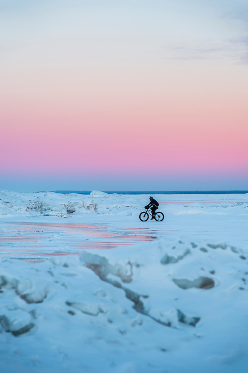 A winter cyclist on a fat bike rides frozen Lake Superior near the Marquette Lighthouse in Marquette, Michigan.
