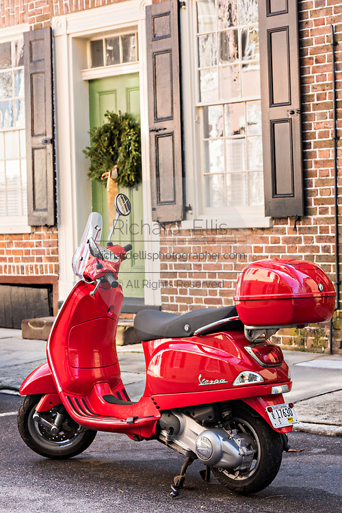A red Vespa scooter parked in front of a historic home decorated with a Christmas wreath on Tradd Street in Charleston, SC.