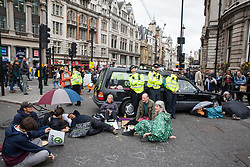 London, UK. 7 October, 2019. Climate activists from Extinction Rebellion use a hearse carrying a coffin and lock-ons to block access from Whitehall from Trafalgar Square on the first day of International Rebellion protests to demand a government declaration of a climate and ecological emergency, a commitment to halting biodiversity loss and net zero carbon emissions by 2025 and for the government to create and be led by the decisions of a Citizens' Assembly on climate and ecological justice.