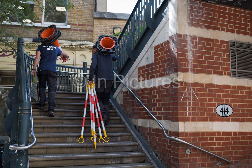 Climbing steps at Blackfriars, workmen carry cones and equipment necessary for overhead work in the City of London, the capitals financial district aka the Square Mile, on 22nd August 2019, in London, England.