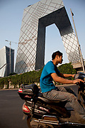 Moped passing the CCTV Headquarters is a 234m 44-storey skyscraper in the Beijing Central Business District or CBD. Affectionately known by the Chinese locals as The Underpants Building due to it's unique design. The tower serves as headquarters for China Central Television. Construction began in 2004 and the building's facade was completed in 2008. After the construction having been delayed as result of a fire which in February 2009 engulfed the adjacent Television Cultural Center, the Headquarters has been finally completed in May 2012. Rem Koolhaas and Ole Scheeren of OMA were the architects in charge for the building, while Arup provided the complex engineering design.