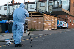 A forensics investigator photographs an adjacent side street   following a stabbing at a Costa Cafe On Bowes Road, Arnos Grove, in which a male victim has been left in critical condition. Arnos Grove, North London, November 12 2018.