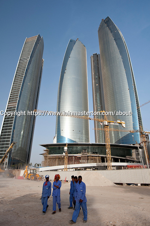 Construction workers at building site of new high rise office towers in Abu Dhabi United Arab Emirates UAE
