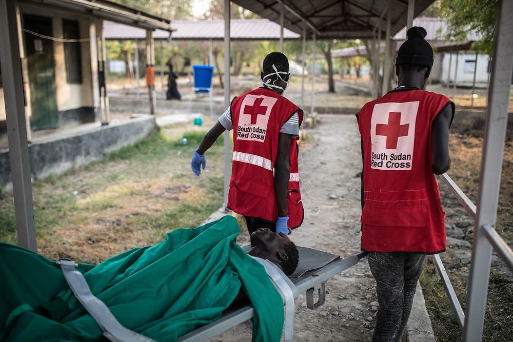 South Sudan Red Cross volunteers carry a patient back to the ward after a surgery. South Sudan, 2020.