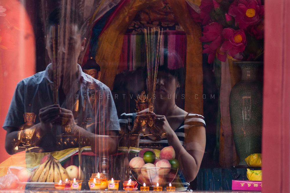 Couple performing prayer at the Lama Temple, Beijing, China