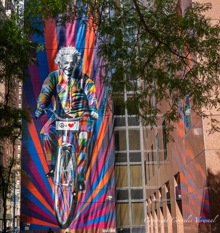 """Mural titled """"Genius is to Bike Ride"""" by Brazilian artist Eduardo Kobra known as """"Kobra"""" Einstein is on a bike with a sign indicating that peace equals squared love."""
