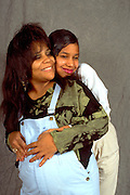 African American daughter and pregnant mother embracing ages 15 and 45.  St Paul Minnesota USA