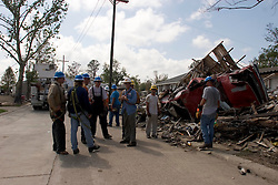 04 Oct, 2005. New Orleans, Louisiana. Hurricane Katrina aftermath. <br /> Private contractor power engineers from the International Brotherhood of Electrical Workers, local 104 from Boston work to restore services amidst the smashed homes in the Arabi neighbourhood. <br /> Photo; ©Charlie Varley/varleypix.com
