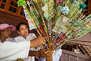 29 JUNE 2014 - DAN SAI, LOEI, THAILAND: A woman donates Thai Baht to Wat Ponchai during a merit making on the last morning of the Ghost Festival. Phi Ta Khon (also spelled Pee Ta Khon) is the Ghost Festival. Over three days, the town's residents invite protection from Phra U-pakut, the spirit that lives in the Mun River, which runs through Dan Sai. People in the town and surrounding villages wear costumes made of patchwork and ornate masks and are thought be ghosts who were awoken from the dead when Vessantra Jataka (one of the Buddhas) came out of the forest. On the last day of the festival people participate in merit making ceremonies at the Wat Ponchai in Dan Sai and lead processions through town soliciting donations for the temple.    PHOTO BY JACK KURTZ
