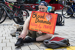 London, UK. 5th June, 2021. An environmental activist from Earth Strike UK sits in Trafalgar Square with a sign referring to the blood diamonds trade during a protest against Anglo-Australian multinational metals and mining corporation Rio Tinto. Rio Tinto produces aluminium, iron ore, copper, uranium, coal, titanium and diamonds and has for many years been linked by activists to a series of adverse environmental and human rights impacts around the world.