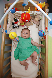 Chinese baby lying in cot
