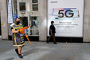 A man walking through the streets advertising a nearby salad and takeaway business, passes-by a Samsung 5G advert outside a phone shop in the City of London, on 1st September 2020, in London, England.