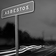 Cars streak by a sign at night on the outskirts of the town of Asbestos, Quebec, Canada. The infamous town of Asbestos is known internationally for it's association with asbestos mining..(Credit Image: © Louie Palu/ZUMA Press)..