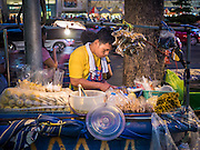 20 MAY 2015 - BANGKOK, THAILAND: A street food vendor grills vegetables while an electric light illuminates his stand. In 2013, the Bangkok Metropolitan Region consumed about 40 per cent of the Thailand's electricity, even though the BMR is only 1.5 per cent of the country's land area and about 22 per cent of its population. Most of the electricity consumed in Bangkok is generated in Laos and Myanmar.   PHOTO BY JACK KURTZ