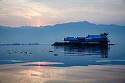 Calm at sunrise on Lake Inle over the Government Rest House hotel. Sitting in one of the typical slender wooden canoes you are very close to the water and have a great sense of perspective over the lake (albeit with the occasional fisherman or taxi buzzing past)
