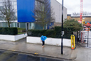 A person pauses outside business premises with a blue exterior, to put on a blue plastic cagoule poncho over their head in a Brixton street, on 15th March 2021, in London, England.
