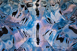 """© Licensed to London News Pictures. 14/03/2019. LONDON, UK. Artist Laura Buckley poses in her work """"Fata Morgana"""", 2012, a giant kaleidoscopic artwork featuring projection using a video recorded on a smartphone. Preview of Kaleidoscope, a new exhibition at the Saatchi Gallery featuring the work of 9 contemporary artists.  The show runs 15 March to 5 May 2019.  Photo credit: Stephen Chung/LNP"""