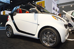 "08 February 2012:  2012 SMART ForTwo Passion Cabriolet: Designed and engineered by Mercedes-Benz, the 2012 Smart ForTwo is the ultimate expression of efficiency through design and innovation. Available in three gasoline-powered models, as well as the fully-electric ForTwo, the Smart provides a solution for environmental efficiency including conservation of material, space and natural resources. Trim levels include the Pure Coupe, Passion Coupe, Passion Cabriolet and Electric Drive model. Powering the 1,808 lb automobile is a one-liter, in-line three-cylinder gasoline engine that creates 70 horsepower and 68 lb. Ft. of torque to the rear-wheels. The Electric Drive uses a 51-kW electric motor with lithium-ion battery that generates 41 hp. All Smart ForTwos come mated to a five-speed smartshift transmission with automatic (for ease) and manual (for fun) modes. Cargo room for the two-seater is a surprising 12. cu. ft. Since safety is paramount, the TwoFour comes packed with features including the protective ""tridion safety cell,"" to help ensure crash compatibility with larger passenger cars, plus electronic stability program, anti-lock braking system and eight airbags Chicago Auto Show, Chicago Automobile Trade Association (CATA), McCormick Place, Chicago Illinois"