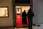 Nada Barghouth, the manager of Amman Center of Homs League Abroad talks to an another employee in front of the prayer room at Homs League Abroad in Amman, Jordan on December 12th, 2018.
