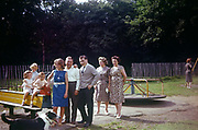 Families and friends have their photo taken in a childrens' playground in the early nineteen sixties. The adults pose for the amateur photo in sunshine, dressed casually for a daytrip to see relatives in another town. The mothers stand back to talk together while a father and son stand in front while a big sister holds on to the childrens' rocking horse on which sits two young children. The picture was recorded on Kodachrome (Kodak) film in about 1961.