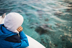 Boy admiring seascape from boat, Mauritius