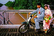 Wedded bliss, a newly married couple rumble over one of the hundreds of canals that crisscross the Mekong Delta.  © Steve Raymer