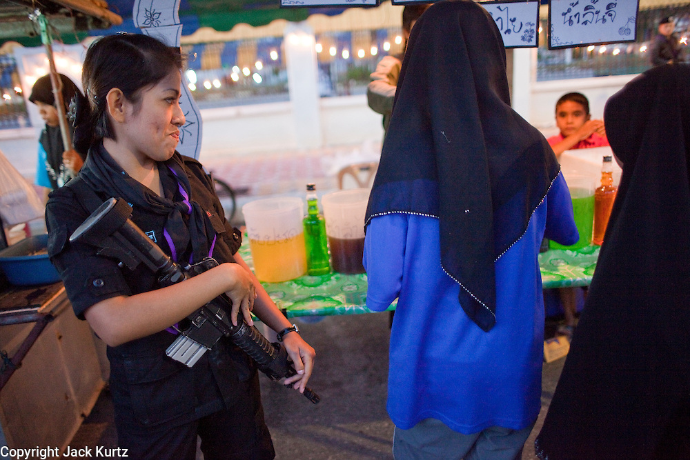 Sept. 29, 2009 -- YARANG, THAILAND: A member of Thailand's women's Ranger unit watches Muslim shoppers in the night market in Yarang, Thailand. The 39 women in the 44th Army Ranger Regiment are the only Thai women seeing front line active duty against Moslem insurgents in Thailand's deep south provinces of Pattani, Narathiwat and Yala. All of the other women serving in Thai security services are employed as office and clerical workers. The Ranger women are based at the Ranger camp in the Buddhist village of Baan Trokbon in Sai Buri district of Pattani province. The unit was formed in 2006 after Muslims complained about the way Thai soldiers, all men, treated Muslim women at roadblocks and during security sweeps. The women are frequently called upon to back up Thai regular army units when they are expected to encounter a large number of Muslim women. At least two of the women have been killed by Muslim insurgents. The unit has both Muslim and Buddhist members. Many of the women in the unit joined after either their fathers or husbands were killed by insurgents.  Photo by Jack Kurtz / ZUMA Press