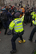 A police officer who used pepper spray against protestors appears to be targeting members of the press and photographers while his colleagues scuffles and argue with demonstrators during clashes following a 'Kill the Bill' protest outside the Houses of Parliament in London on Saturday, April 3, 2021. Projectiles were thrown as police pushed protesters away, and dozens of extra officers were brought in to help unblock the road for a McDonald's lorry held up outside parliament. (Photo/ Vudi Xhymshiti)